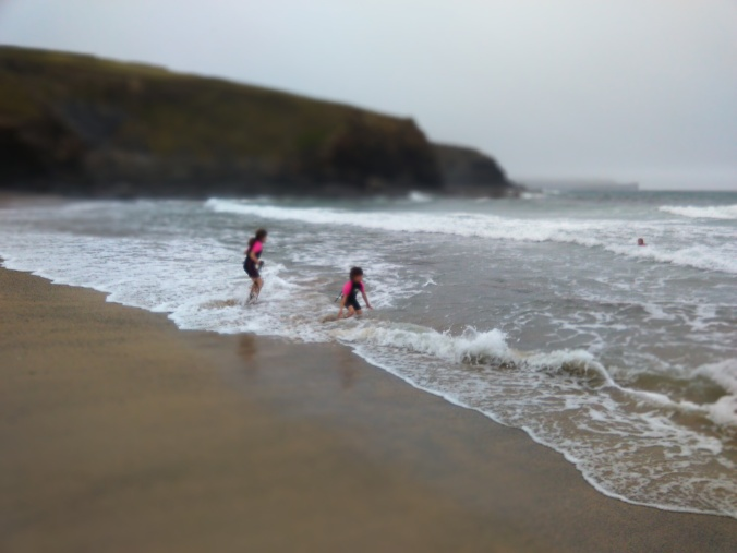 Emily and Ruby in the surf at Gunwalloe Church Cove2